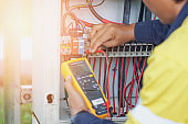 Workers use a Multimeter to measure the voltage of electrical wires produced from solar energy to confirm systems working normally