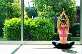 Attractive fit young yogi woman wearing sportswear sitting in vajrasana exercise, seiza pose with namaste home. Female stretching at yoga center class, full length windows, garden view. Background, copy space.