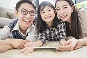 happy asian family spending time together on sofa in living room. family and home concept