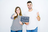 Young couple holding blackboard with our first home text over white isolated background happy with big smile doing ok sign, thumb up with fingers, excellent sign