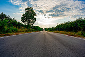 Long road street on forest and sky background