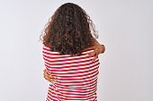 Young brazilian woman wearing red striped t-shirt standing over isolated white background Hugging oneself happy and positive from backwards. Self love and self care