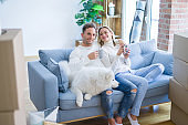 Young beautiful couple with dog sitting on the sofa drinking coffee at new home around cardboard boxes