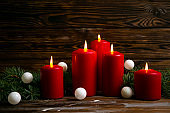 Bunch of candles burning over textured background.