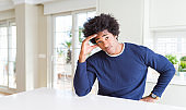 Young african american man wearing casual sweater sitting at home worried and stressed about a problem with hand on forehead, nervous and anxious for crisis