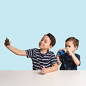 Two children are taking selfie in front of blue background