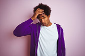 Young african american man wearing purple sweatshirt standing over isolated pink background worried and stressed about a problem with hand on forehead, nervous and anxious for crisis