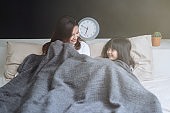 Happy mom and her daughter girl play in bedroom