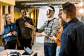 Business team of multiracial people working on virtual reality applications and games, young excited man testing VR glasses or goggles standing in the office room with colleagues