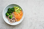 Vegan bowl of noodles, broccoli, edamame and carrots