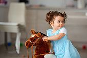 Girl  in a dress playing on her rocking horse
