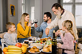 big family with children having delicious thanksgiving dinner together at home while old grandfather cutting turkey and young parents clinking wine glasses