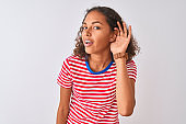 Young brazilian woman wearing red striped t-shirt standing over isolated white background smiling with hand over ear listening an hearing to rumor or gossip. Deafness concept.