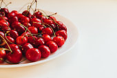 Plate with sweet cherries closeup