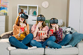 Three young attractive women wearing headset VR virtual reality vision goggles watching video, sitting on the sofa and eating popcorn in cozy room