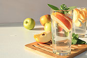 Apple cider, juice or fruit drink in a glass on a sunny table. The concept of diet and weight loss. Apples help cleanse the body and reduce weight.