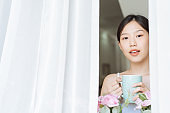 Portrait Asian woman relaxing with coffee at home
