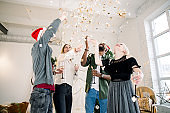 Multiracial group of friends making big New Year party at home. Four people throwing confetti and drinking champagne in front of Christmas decorations
