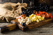 Assorted cheeses on wooden board plate. Camembert cheese, cheese grated bark of oak, hard cheese slices, walnuts, grapes, bread, thyme, top view. Cheese and wine. Antipasto. Red wine