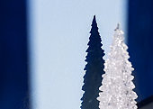 Blurred White Shiny Souvenir Christmas Tree and Its Silhouette, Shadow on Blue Background.