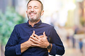 Middle age hoary senior man over isolated background smiling with hands on chest with closed eyes and grateful gesture on face. Health concept.