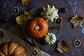 Pumpkin on a plate. Autumn cozy background with leaves, vanilla.