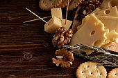 Pieces of cheese, nuts, raisins, snacks for wine on a wooden background. Appetitive