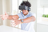 African amaerican man having fun playing with virtual reality glasses