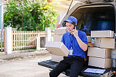 Young delivery man in blue uniform phone talking to customers to deliver the goods.