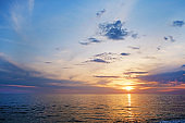 Beautiful seascape of sun setting over calm azure water with wind patterns and clear blue orange gradient sky without clouds. Ocean view with horizon, background with a lot of copy space for text.