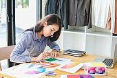 Asian woman fashion designer work at home happily. Internship designer about fashion clothing.