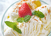 Vanilla ice cream decorated with mint leaves and ripe strawberries, sprinkled with cinnamon