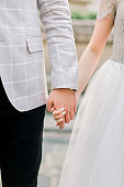 Cropped image of young wedding couple holding hands, wedding ceremony day. Hands of the man and woman in love