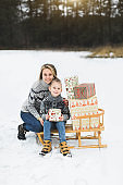 Mother and son in gray knitted sweaters enjoying beautiful winter day outdoors. Son is sitting on wooden sledge decorated with nice Christmas Santa presents