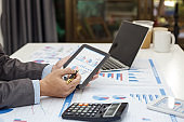 Close up businessman using calculator and tablet in the calculations revenue and market statistics.