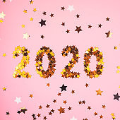 2020 New Year symbol of gold confetti on pink ackground.