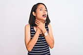 Young chinese woman wearing striped t-shirt standing over isolated white background shouting and suffocate because painful strangle. Health problem. Asphyxiate and suicide concept.