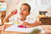 Beautiful african american toddler sitting painting car toy using marker pen on desk at kindergarten