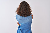 Young brazilian woman wearing denim shirt standing over isolated white background Hugging oneself happy and positive from backwards. Self love and self care