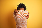 Afro man with dreadlocks wearing striped t-shirt standing over isolated yellow background Hugging oneself happy and positive from backwards. Self love and self care