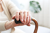 Old age woman with health problems resting her arms on walking cane.
