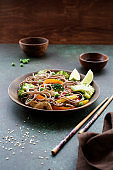 Stir fry noodles with chicken meat and vegetables in bowl on dark green background copy space