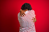 Young afro man with dreadlocks wearing striped t-shirt standing over isolated red background Hugging oneself happy and positive from backwards. Self love and self care