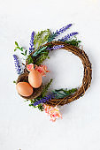 Easter concept. Bright spring flowers, wreath with easter eggs on a light background