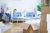 Young beautiful couple with animal moving sofa at new home around cardboard boxes