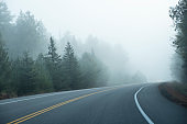 Car Driving Through Thick Fog With Its Headlights