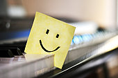 Close-up of smiley face on yellow sticky note for memos place between white and black piano keys with the background out of focus indoors during daylight