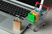 Buying goods and clothing in the online store. Shopping bags in shopping cart on laptop keyboard