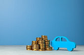 Car and a stack of coins. Concept car purchase or insurance. Blue background.