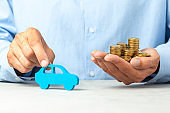 Man in blue shirt is holding car and stack of coins. Concept car purchase, taxes or insurance